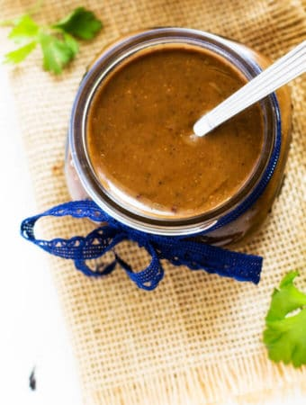 Photo of a Balsamic Vinaigrette Dressing Recipe in a glass jar with a blue ribbon sitting on a rustic fabric.