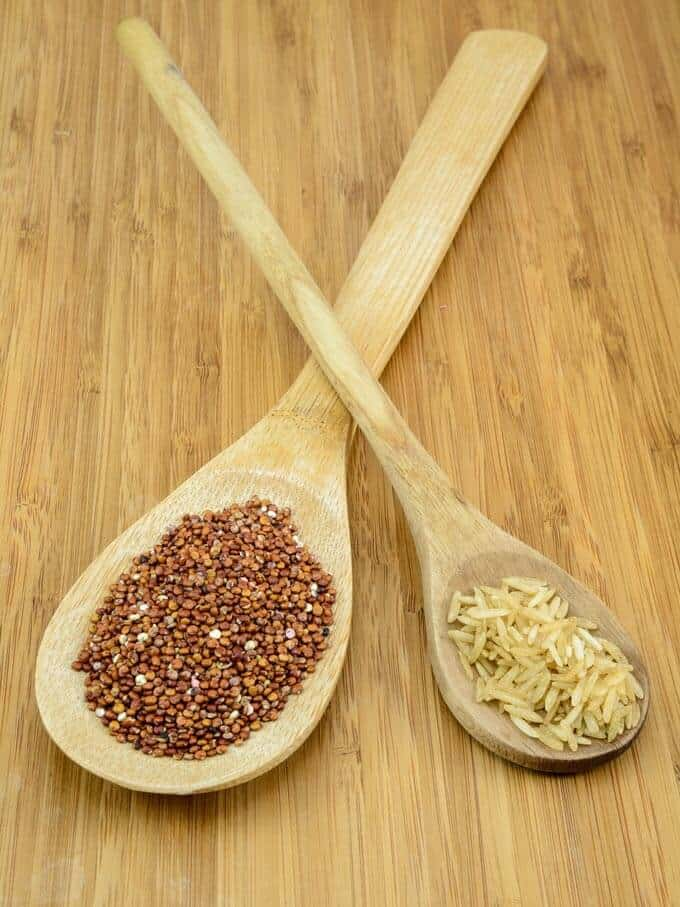 Photo of quinoa and rice in wooden spoons.