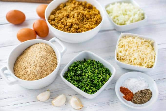 Photo of Ingredients in small white bowls: Quinoa, eggs, onion, gluten free breadcrumbs, garlic, parsley, seasonings and parmesan.