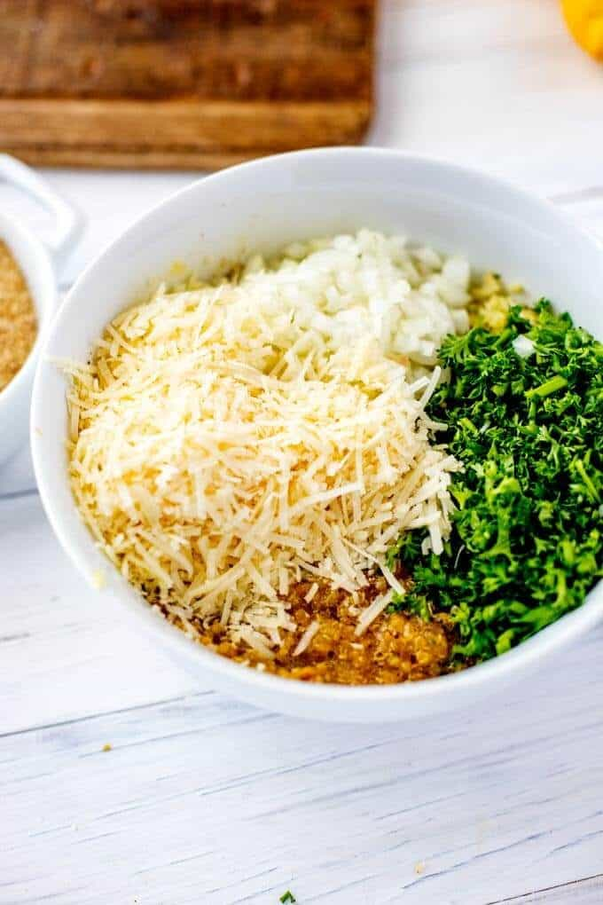 Photo of cooked quinoa, eggs, cayenne pepper, salt, black pepper, chives, Parmesan, and garlic in a white bowl.