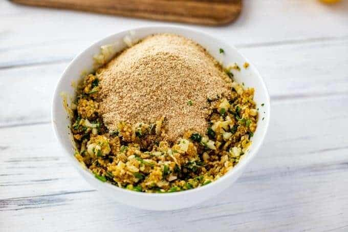 Photo of breadcrumbs being added to other ingredients for quinoa cakes.