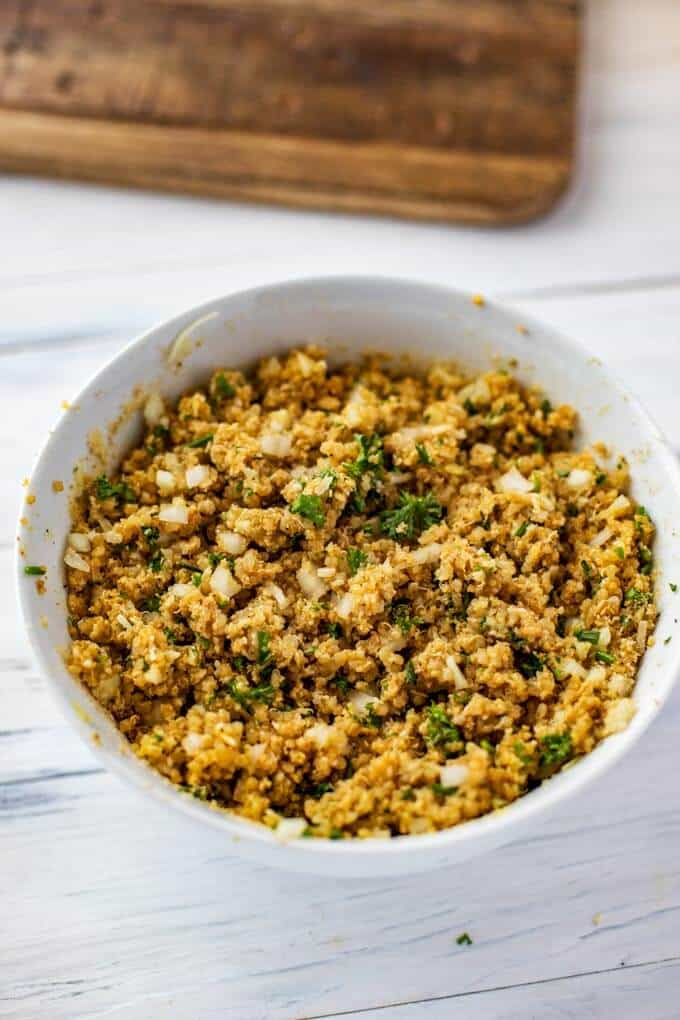 Photo of cooked quinoa, eggs, cayenne pepper, salt, black pepper, chives, Parmesan, garlic, and gluten free breadcrumbs in a white bowl.