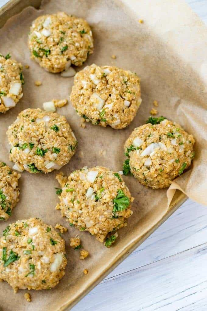 Photo of uncooked quinoa patties formed on a parchment lined baking sheet.