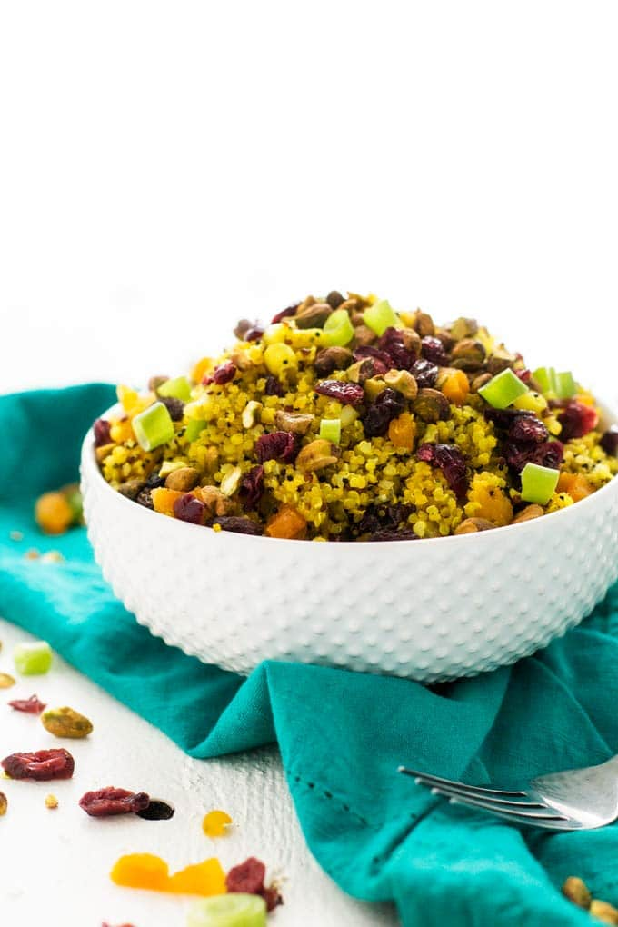 Side shot of Jeweled Quinoa Salad in a white bowl on a turquoise napkin