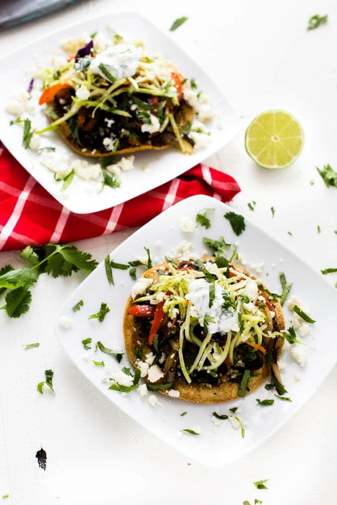 Two plates of Black Bean and Quinoa Tostadas with a lime garnish.