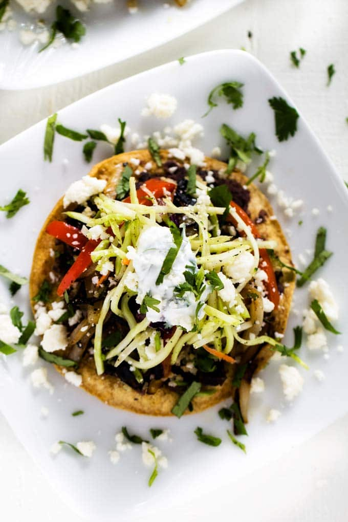 Overhead view of Black Bean and Quinoa Tostadas on a white plate.