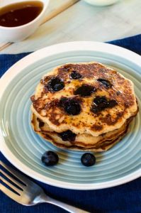 Blueberry Quinoa Pancakes on a blue plate.