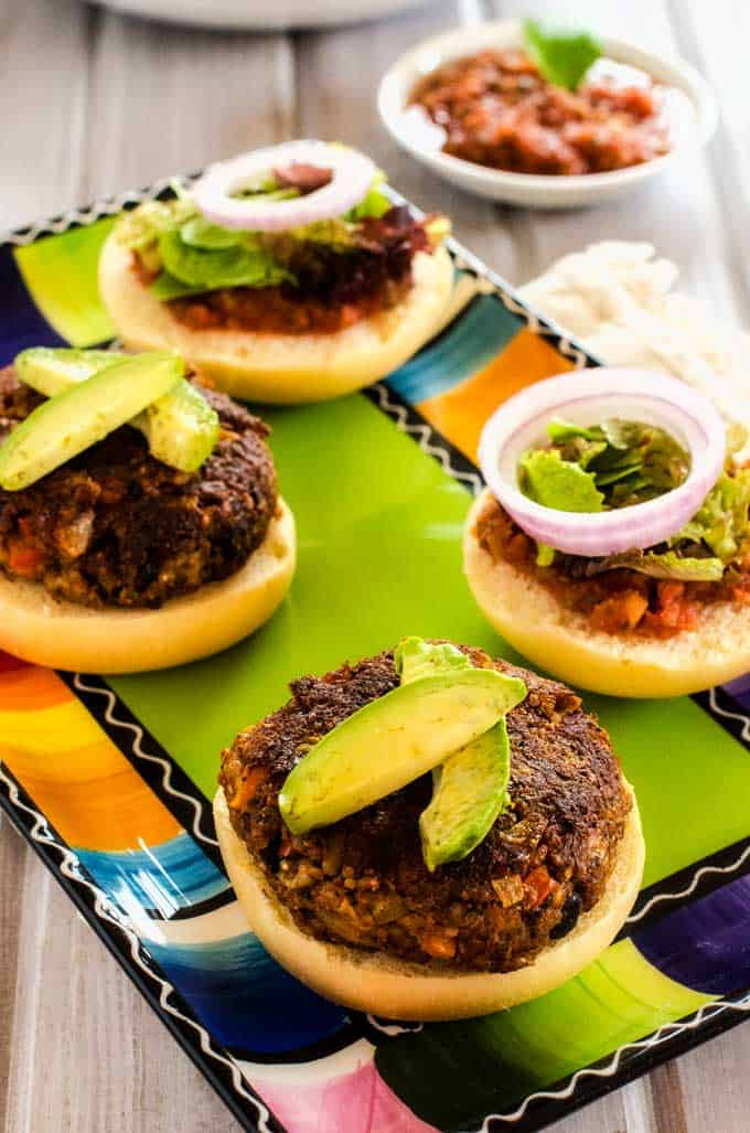 Photo of two Quinoa Burgers on buns garnished with avocado sitting on a colorful plate.