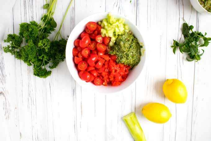 Overhead photo of measured tomatoes, quinoa, chopped cucumber and the dressing for a quinoa tabbouleh recipe.