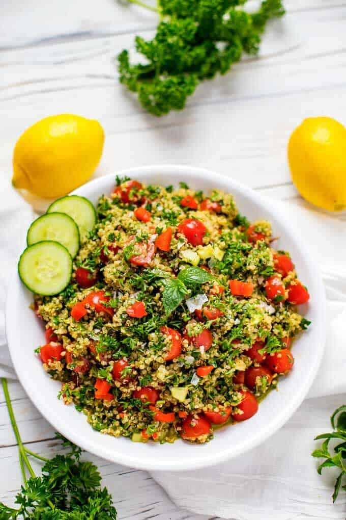 Overhead photo of a shallow bowl of Quinoa Tabbouleh garnished with mint with mint, parsley and lemons scattered around.