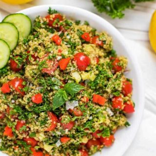 Overhead photo of a shallow serving dish with Quinoa Tabbouleh garnished with mint and cucumber.