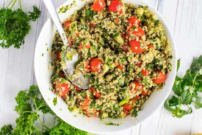 White bowl with quinoa, cucumber and the dressing for a quinoa tabbouleh recipe.