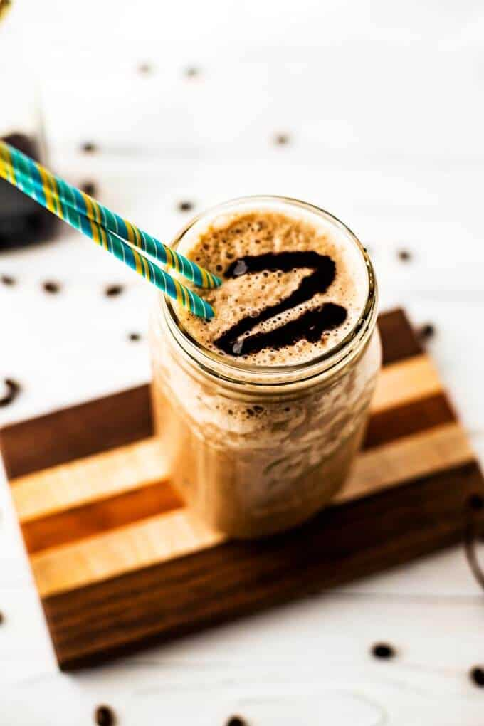 Photo of a Quinoa Smoothie with coffee in a mason jar with a blue and yellow striped jar.