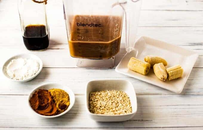 Photo of liquid ingredients for a quinoa smoothie in the blender surrounded by dry ingredients in small dishes.
