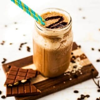 Vertical image of coffee quinoa smoothie in a mason jar sitting on a cutting board.