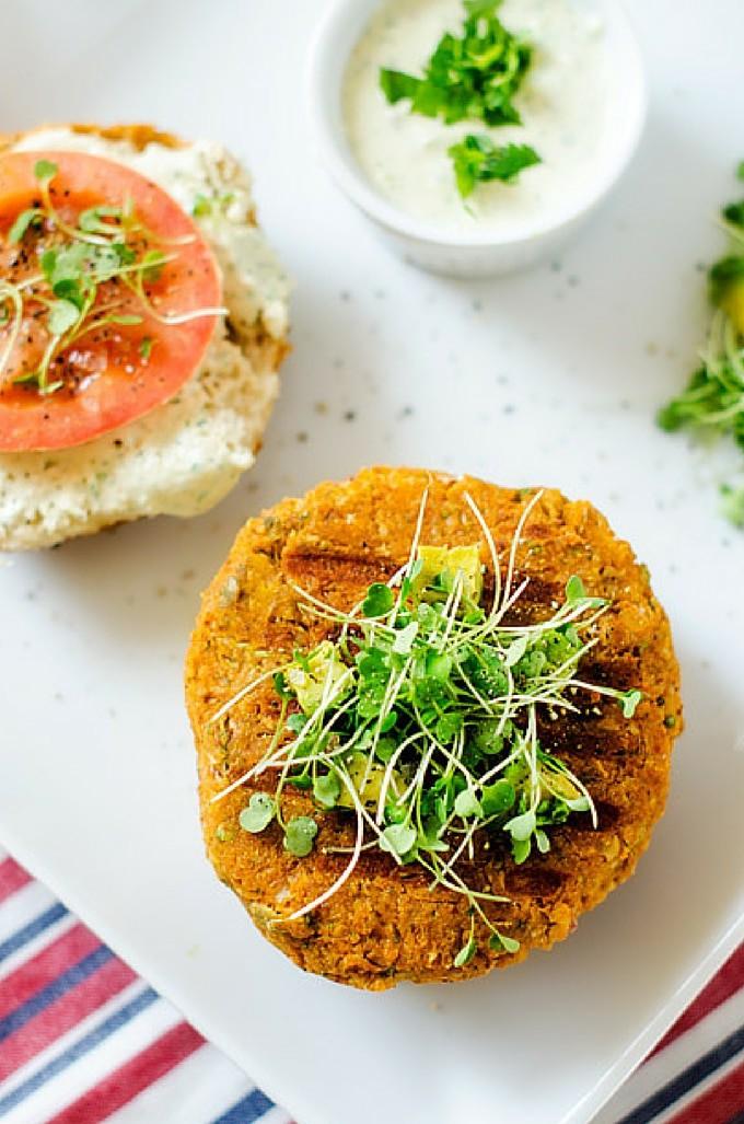 Overhead photo of a Sweet Potato Burger on a bun garnished with microgreens with the other half of the bun sitting next to it with a tomato and microgreens.