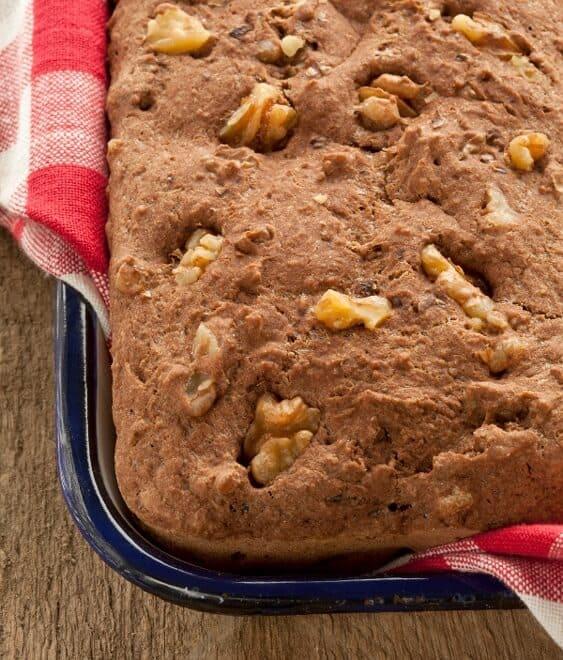 Photo of Walnut Cinnamon Quinoa Loaf in a bread pan against a dark background.