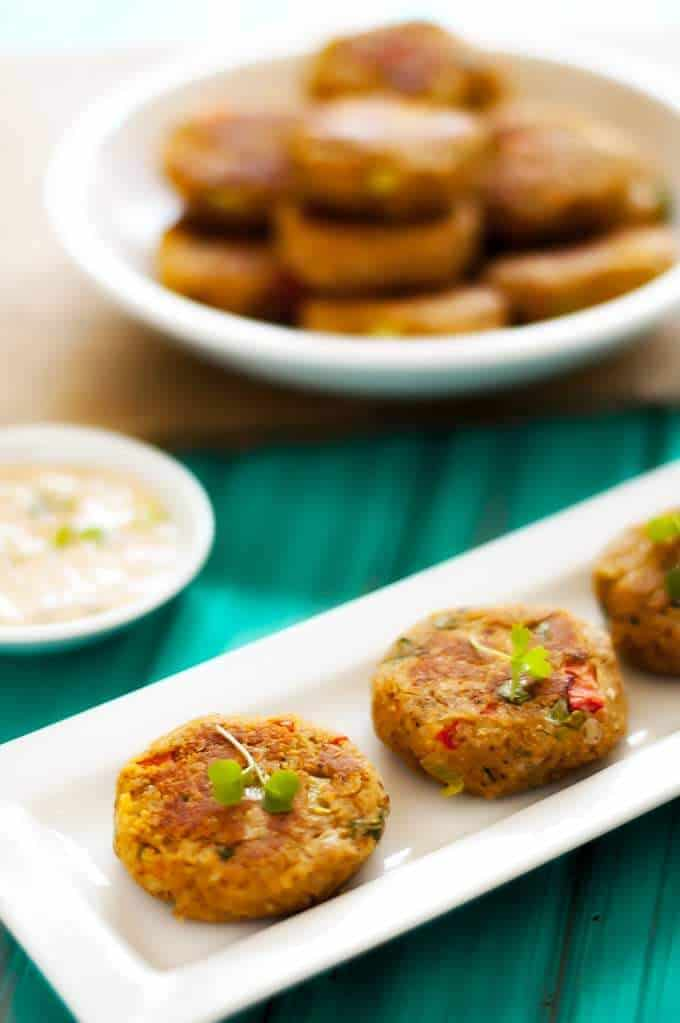 Two Chickpea Quinoa Cakes with Creamy Cucumber Sauce with a bowl in the background.