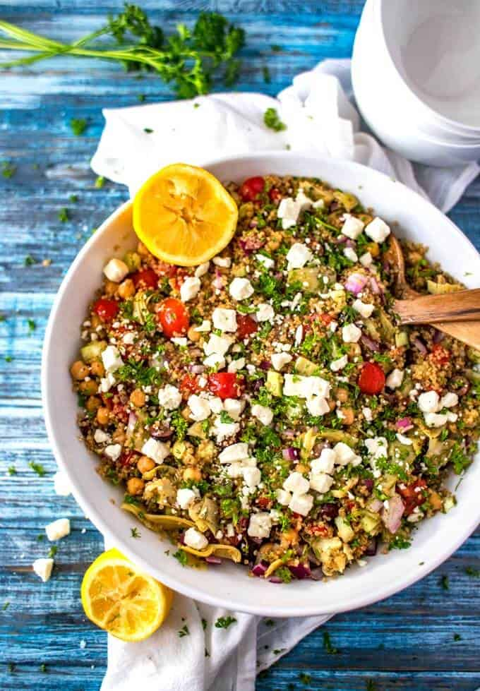 Overhead photo of Mediterranean Quinoa Salad in a large white bowl with wooden serving utensils.