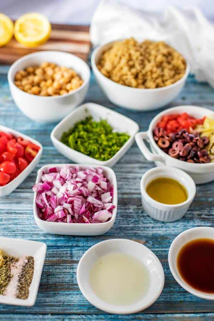 Photo of Quinoa Mediterranean Salad Ingredients gathered in small white dishes sitting on a blue background.