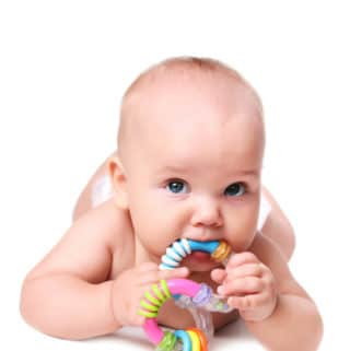 Photo of a baby with a teething ring laying on his stomach on a white background.