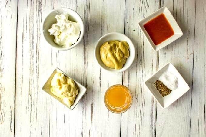 Photo of mayo, Greek yogurt, apple cider vinegar, Dijon mustard, sweetener, hot sauce, sea salt, and celery seeds in small prep bowls.