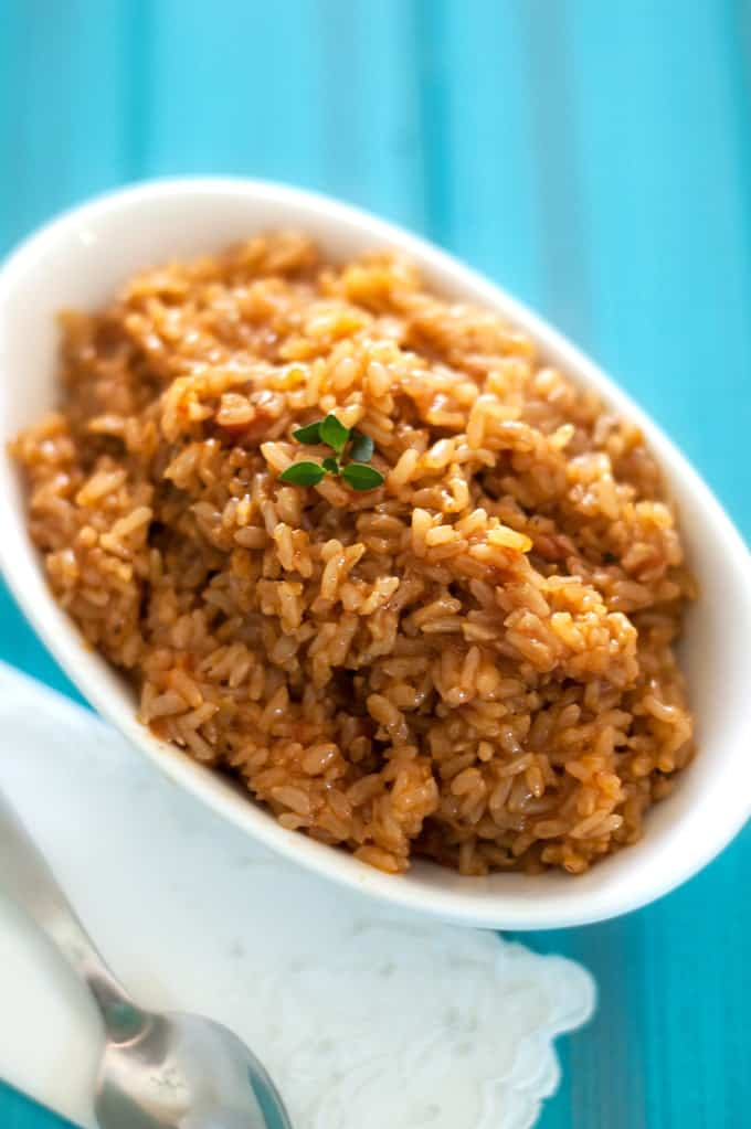 Overhead photo of cooked Spanish Brown Rice in a small white bowl against a blue background.