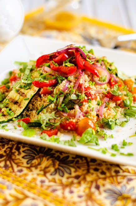Side photo of a grilled vegetable quinoa salad on a white plate garnished with herbs.