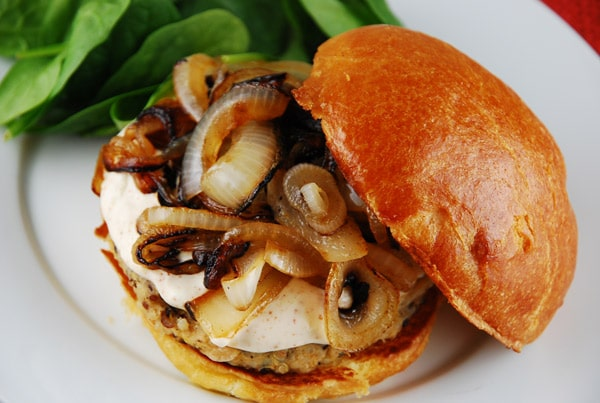 Photo of a White Bean Veggie Burger with Caramelized Onions and Chipotle Lime Mayo on a bun sitting on a white plate.