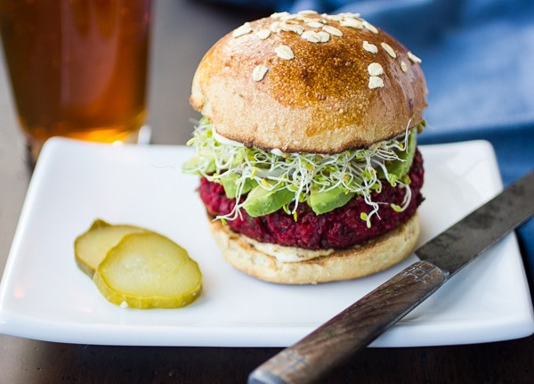 Horizontal image of a prepared Beet Burger Recipe on a bun with avocado and sprouts sitting on a white plate.