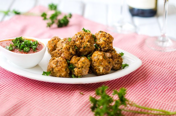 Side photo of Beef and Quinoa Meatballs on a white platter sitting on a red and white napkin.
