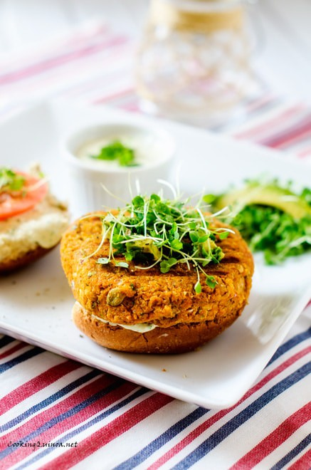Side photo of Sweet Potato Burgers on a white plate sitting in a red, white, and blue napkin.