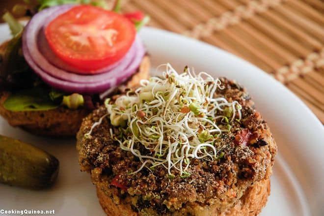 Photo of a Vegan Quinoa Burger on a gluten free english muffin with sprouts on it sitting on a white plate.