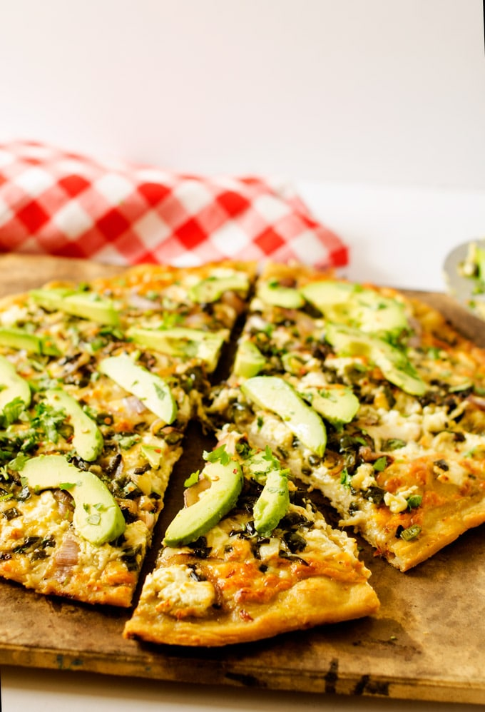 Photo of an Avocado Pizza with PepperJack and Poblano Peppers on a pizza stone against a white background.
