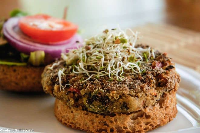 Side photo of a vegan quinoa burger sitting on a gluten free english muffin on a white plate.