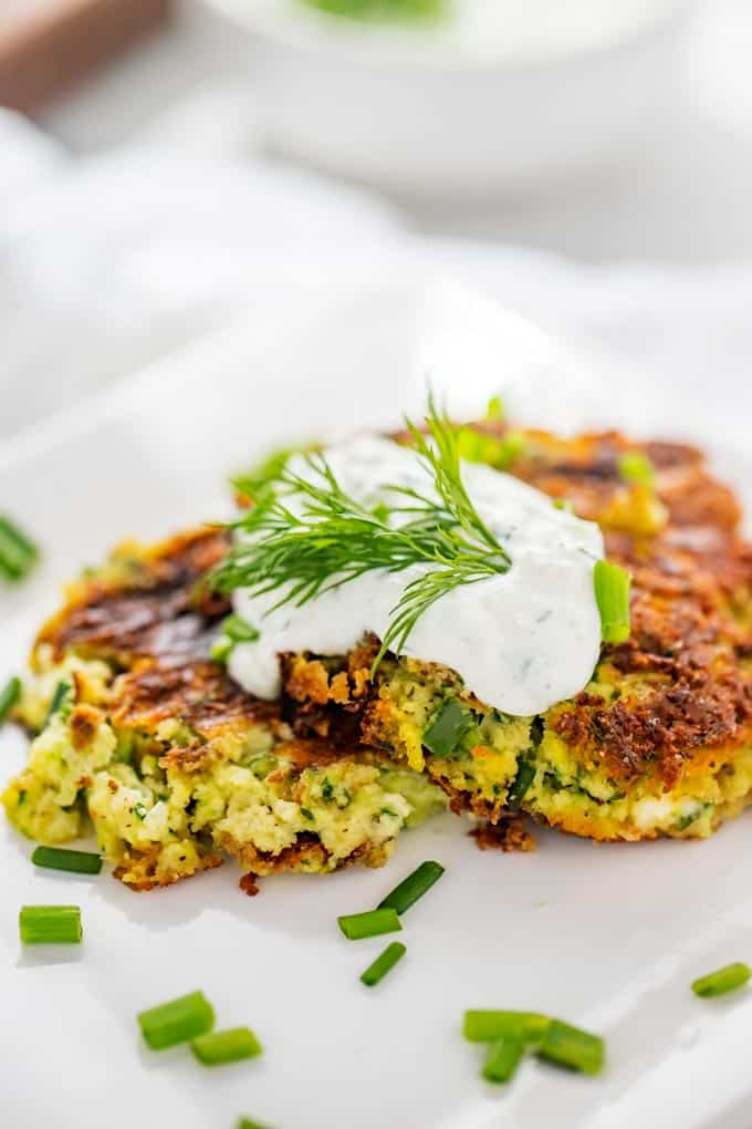 Photo of prepared Zucchini Fritters Recipe with Feta on a white plate.