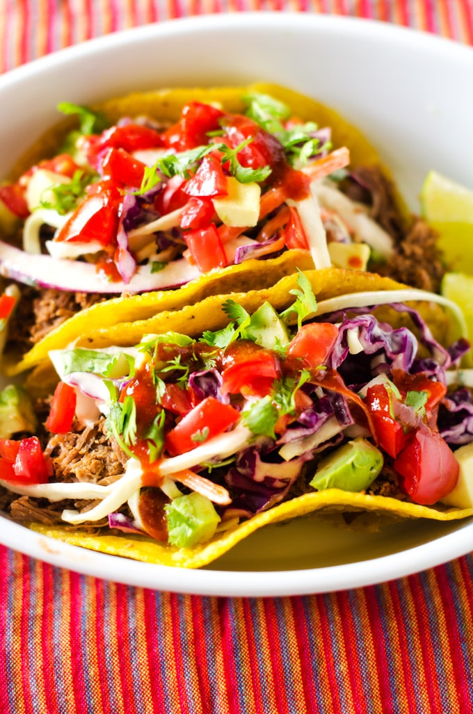 Photo of two Shredded Beef Tacos with Chipotle Lime Slaw in a small white dish.