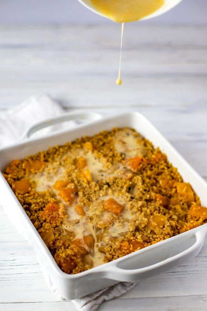Butternut Squash Casserole in a baking dish with the egg mixture being added to the pan.