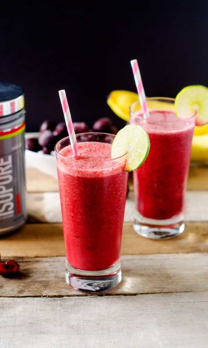 Two Cherry Smoothie Recipes with lime garnishes and cherries and bananas behind them.