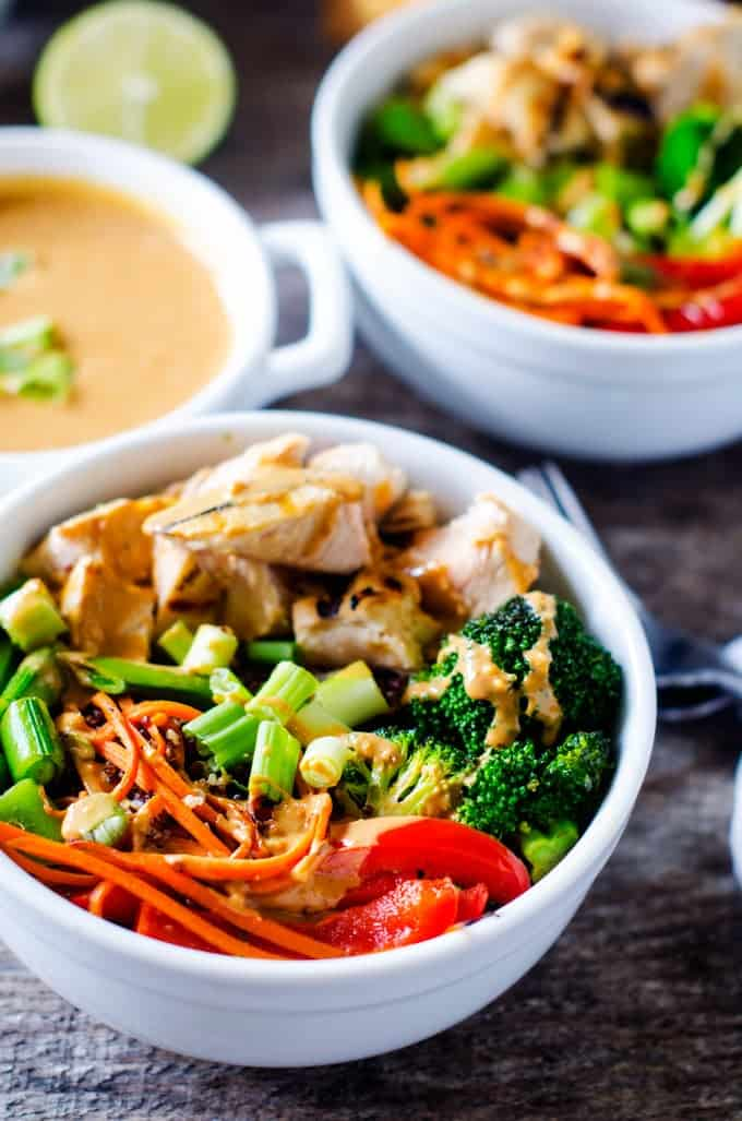 Photo of a prepared Veggie Quinoa Bowl recipe divided among two white bowls with a small dish of a Spicy Peanut Sauce.