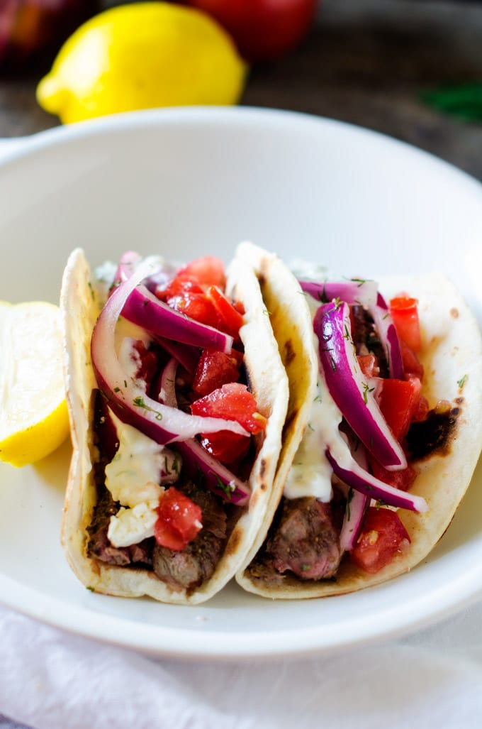 Side photo of a prepared Steak Gyro Recipe on a white plate with a lemon garnish.