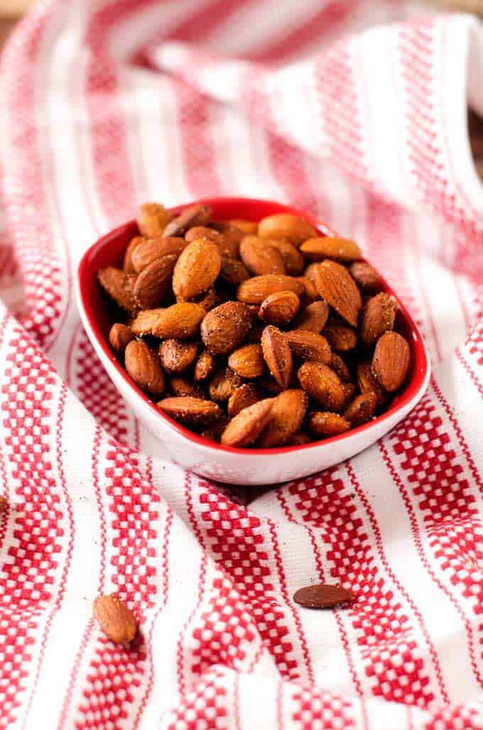 Shot of Spiced Almonds in a small bowl on a red and white tea towel.