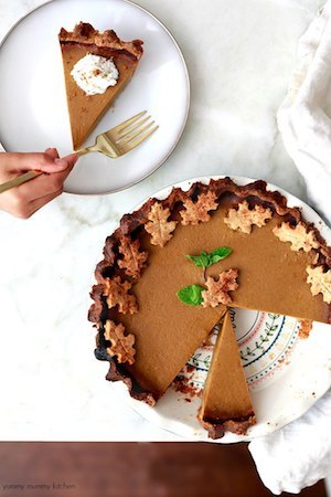 Photo of a vegan pumpkin pie slice at the top with the remainder of the whole pie below.