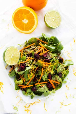 Overhead photo of citrus quinoa salad on a white background garnished with citrus peels.