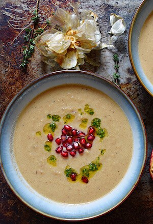 Photo of Creamy Roasted Garlic and Cauliflower Soup in a blue bowl garnished with pomegranates.