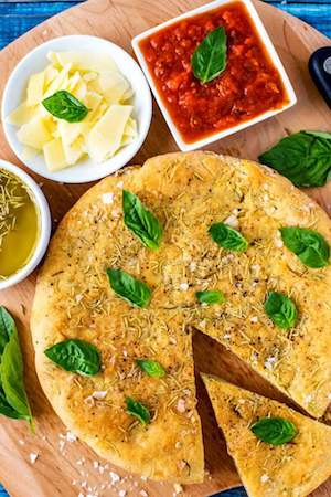 Overhead photo of gluten free Focaccia Bread garnished with basil.