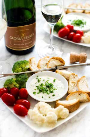 Photo of goat cheese gruyere fondue surrounded by bread cubes and vegetables.
