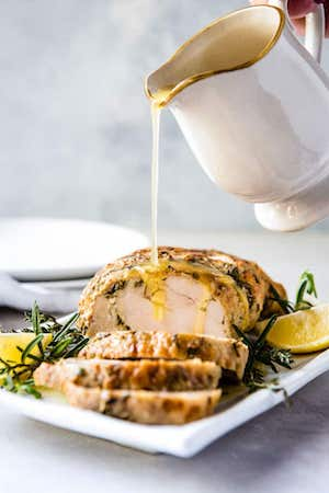 Photo of Instant Pot Turkey Breast on a white serving platter with gravy being poured over it.