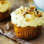 Square side photo of a gluten free pumpkin muffin with cream cheese frosting topped with walnuts.
