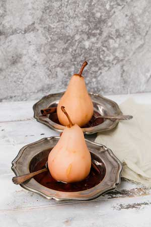 Photo of two cranberry poached pears on silver platters against a light grey background.